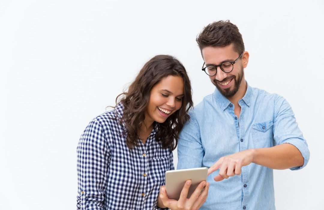 cheerful-couple-watching-content-on-tablet-and-laughing