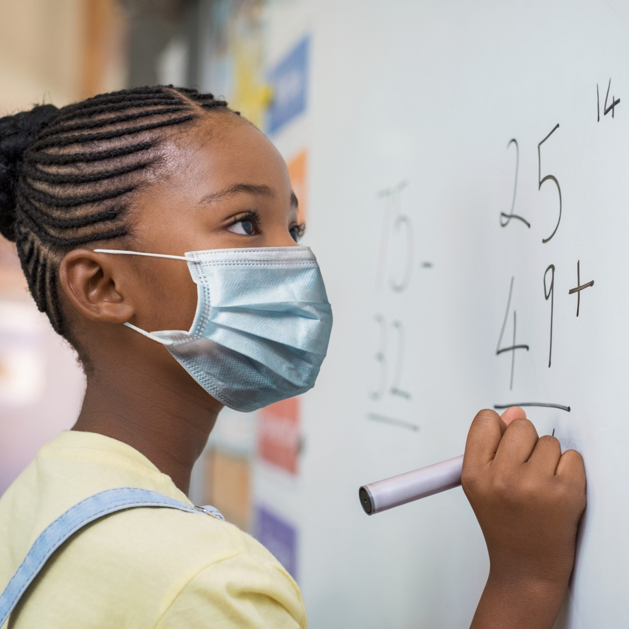 Portrait of african girl wearing face mask and writing solution of sums on white board at school. Black schoolgirl solving addition sum on white board during Covid-19 pandemic. School child thinking while doing mathematics problem and wearing surgivcal mask due to coronavirus.